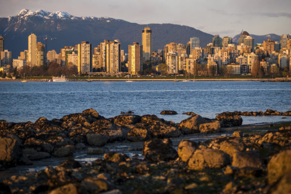 The city of Vancouver, British Columbia is viewed from a distance across English Bay. In the background are the North Shore mountains.